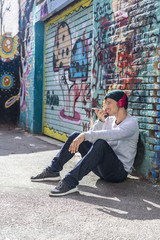 Young man with headphones sitting in front of graffiti wall using cell phone