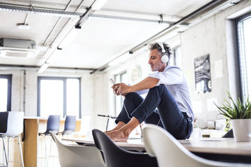 Mature businessman with smartphone and headphones sitting barefoot on desk in office