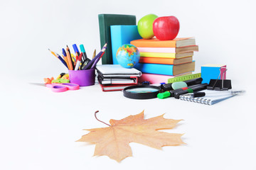 foreground is the maple leaf on the background of school supplies .photo with copy space