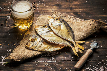 close-up dried fish, vintage glass of beer on a dark wooden background. Top view. Horizontal orientation.