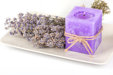 Still life with lavender candle and dry lavender on a white plate on white background