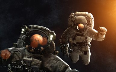 Astronauts in front of Mars. SolarSystem. Image in 5K resolution for desktop wallpaper. Elements of the image are furnished by NASA