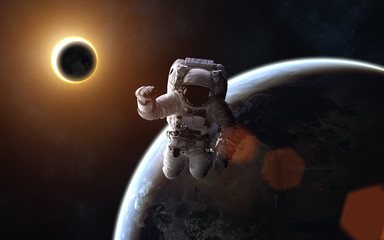 Astronaut. Solar eclipse. Moon and Earth. Image in 5K resolution for desktop wallpaper. Elements of the image are furnished by NASA