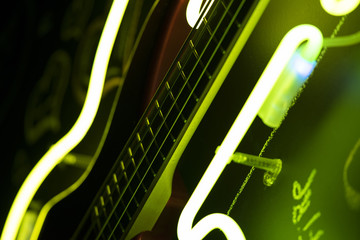 Yellow and green light surrounding bass guitar neck, beautiful background