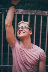 lachender Mann mit rosa Shirt und Brille
