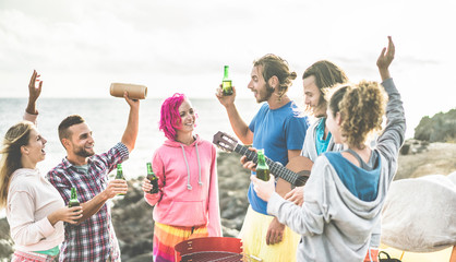 Happy friends dancing and drinking beers in camping party