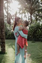 Mama und Tochter küssen sich unter Palmen mit Gegenlicht