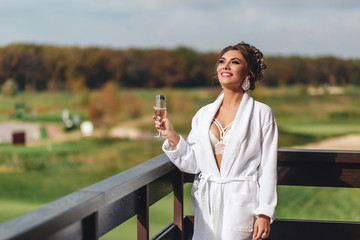 Beautiful young bride is holding a glass of champagne and smile