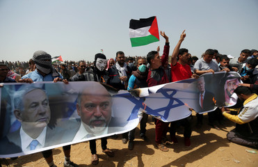 Palestinian demonstrators burn a banner showing a representation of an Israeli flag and pictures of Netanyahu, Lieberman, Trump, and bin Salman during a protest at the Israel-Gaza border, in the southern Gaza Strip