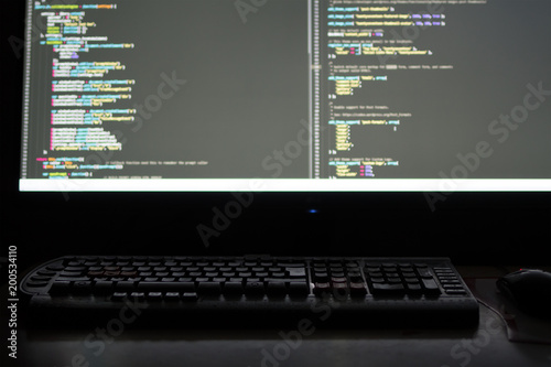 the screen of the programmer working late at night behind a computer