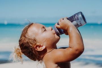 Kind trickt genüsslich aus einer Flasche am Strand
