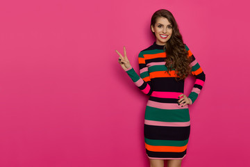 Woman In Multicolored Striped Dress Is Showing Peace Hand Sign And Smiling