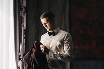 Morning of the groom. Good morning preparation. Young and handsome groom in a wedding shirt holds a jacket in a beautiful interior