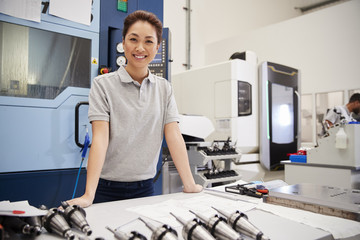 Portrait Of Female Engineer With CAD Drawings In Factory
