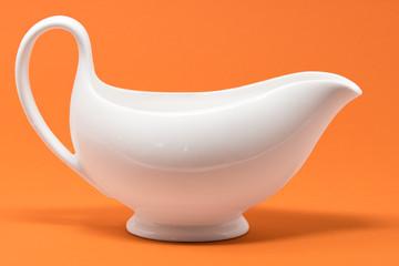 A white jug set against a bright orange background