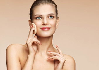 Smiling woman applying powder on her face with cosmetic application. Photo of young woman with beautiful eyes on beige background. Youth and skin care concept
