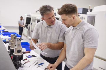 Engineer And Apprentice Discussing Job Sheet In Factory