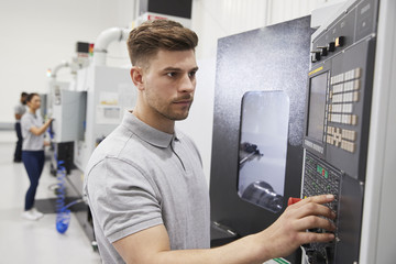 Male Engineer Operating CNC Machinery In Factory Wall mural