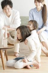 積み木で遊ぶ姉妹を見守る両親