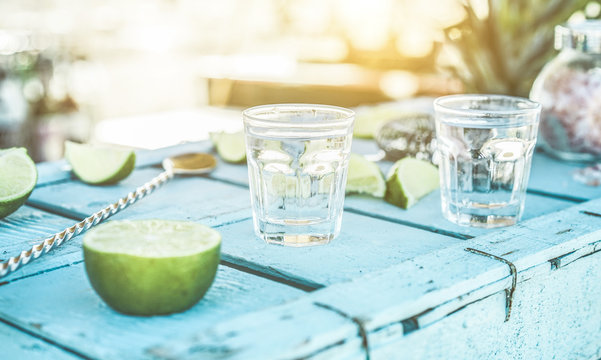 Tequila shots with limes and salt on blue wood bar counter  at sunset