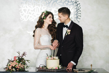 Beautiful bride and groom making a wish as they stand cutting the wedding cake together in an elegant reception venue