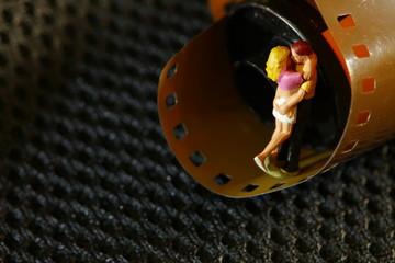 Old fashion film cartridge and miniature figure model scene.