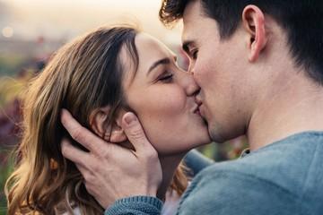 Verliebtes Paar küsst sich während des Sonnenuntergangs