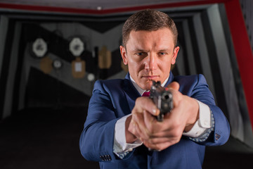 A middle-aged man in a business suit and tie looks like a spy holding a gun in his hands.