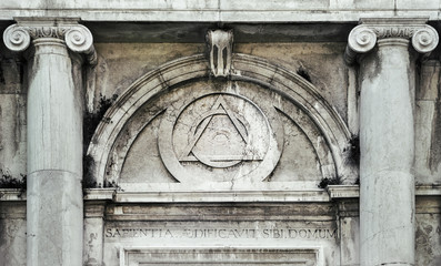 Eye of Providence, inside triangle interlaced with circle above doorway of building in Venice, Italy - It represents the eye of God watching over humanity, or divine providence.