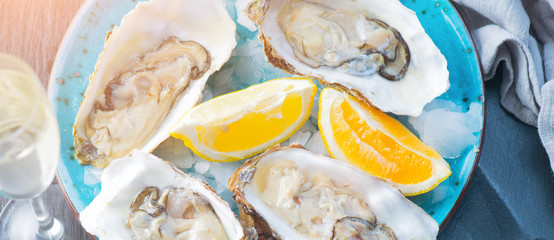 Fresh oysters close-up on blue plate, served table with oysters, lemon and champagne in restaurant. Gourmet food. Top view