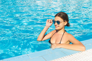 Beautiful woman relaxingin swimming pool Water in sunglasses. Girl With Healthy Tanned Skin