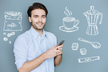 Coffee time. Cheerful young manager standing with a modern smartphone in his hands and dreaming about a cup of tasty coffee