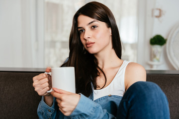 Beautiful young woman drinking cup of coffee at home