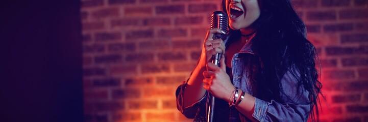 Cheerful singer singing illuminated nightclub Fotobehang
