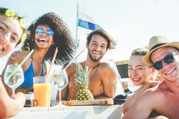 Group of happy friends drinking tropical cocktails at boat party - Young people having fun in caribbean sea tour eating pineapple and laughing - Youth and summer vacation concept