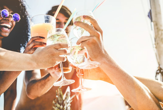 Group of happy friends cheering with tropical cocktails at boat party