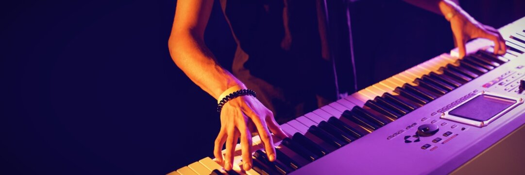 Mid section of male musician playing piano
