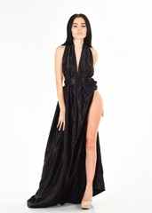 Woman in elegant black long evening dress with decollete, white background. Attractive girl wears expensive fashionable evening dress with erotic slit. Lady, sexy girl in dress. Fashion dress concept.