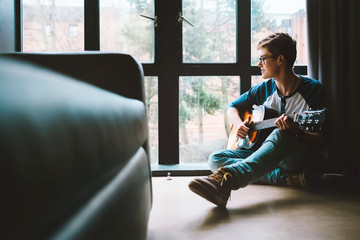 Boy with guitar sits on the floor at cozy home, moody day light