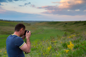 A travel photographer takes pictures of a beautiful landscape at sunset in the warm summer evening.