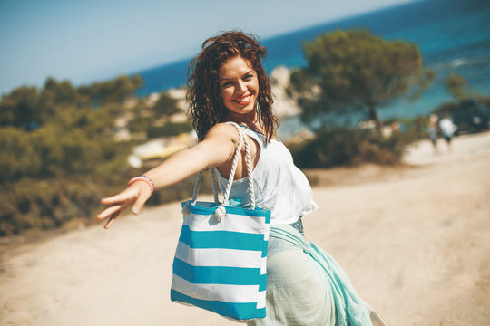 Pretty young woman with a bag on the beach