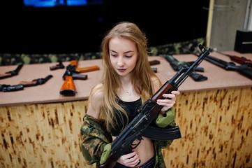 Girl with machine gun at hands on shooting range.