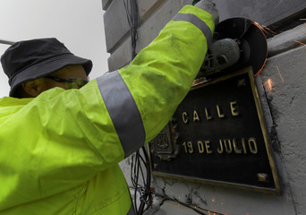 A worker removes street plates with Franco era references, in appliance to Spain's law of Historical Memory which forbids public places or entities to be named with references to Spain's former dictatorship in Oviedo