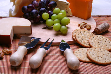 Still life 3 types of cheese roquefort cheese, red and green grapes, crackers, walnuts, cheese utensils on wooden plate