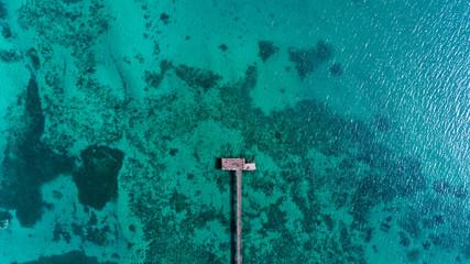Topview Beautiful wood bridge into the tropical sea in summer season (photo from drone)