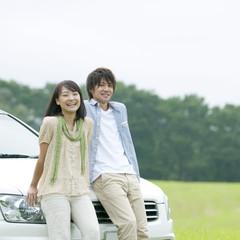 草原で車に寄り掛かり微笑むカップル