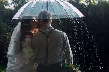 Wedding couple waking by the rain under umbrella