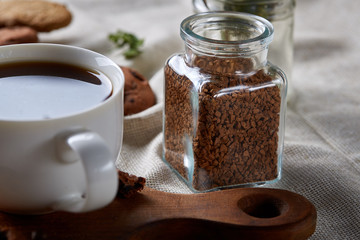 Open jar of instant coffee arranged on woden table, top view, close-up, selective focus.