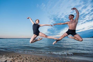 Young guy and girl in black swimwear high jump and dance on the beach in the evening. Street ballet.