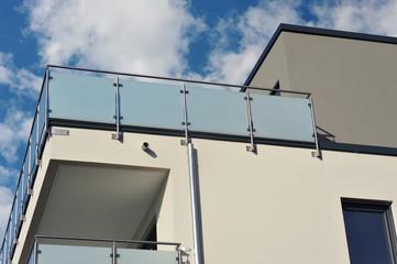 Moderner verglaster Balkon mit Edelstahl-Geländer an Neubau-Hausfront